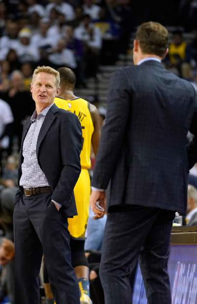 Golden State Warriors coach Steve Kerr, left, talks to Los Angeles Lakers coach Luke Walton during a timeout on the first half of an NBA basketball game Tuesday, Dec. 25, 2018, in Oakland, Calif. (AP Photo/Tony Avelar)