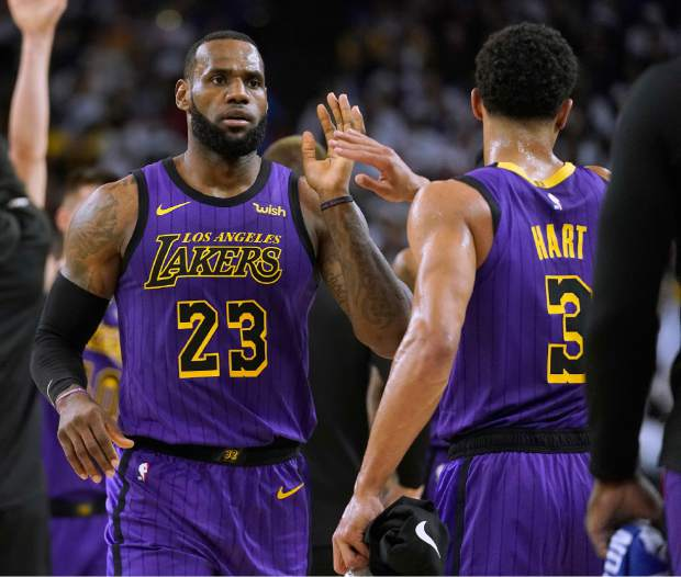 Los Angeles Lakers forward LeBron James (23) high-fives Josh Hart (3) at the end of the first half of the team's NBA basketball game against the Golden State Warriors on Tuesday, Dec. 25, 2018, in Oakland, Calif. (AP Photo/Tony Avelar)