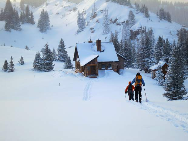 Skiers make their way to the snow-covered Fowler-Hilliard Hut.