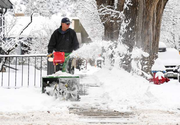 A man clears the sidewalks in front of houses along 10th Street to Colorado Avenue on another snowy morning in Glenwood Springs.