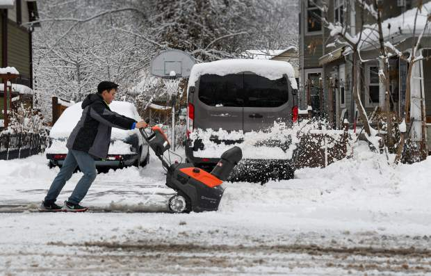 15-year-old Lucas Delrio uses the snow blower to get snow out of the driveway at a residence in downtown Glenwood. He and his brothers spent Christmas shoveling driveways and sidewalks for many of their neighbors.