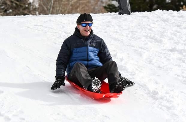 John Michelle is all smiles as he sleds down a hill near Cardiff Glen after another early monring snowstorm in Glenwood Springs.