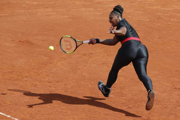 Serena Williams, of the United States, returns a shot against Krystyna Pliskova, of the Czech Republic, during their first round match of the French Open tennis tournament at the Roland Garros stadium in Paris. French tennis authorities said her daring, full-length catsuit would no longer be welcome at the French Open.