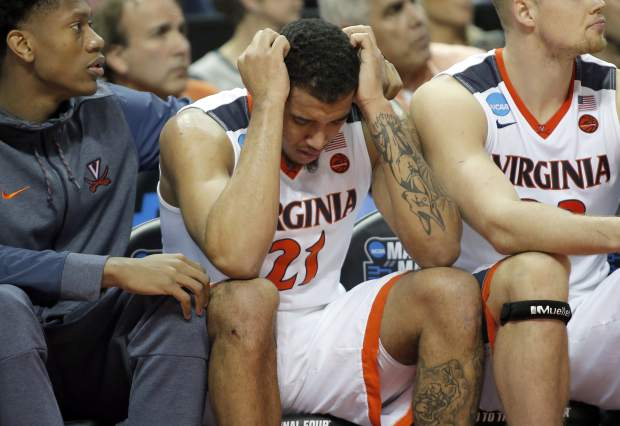 FILE - In this March 16, 2018, file photo, Virginia's Isaiah Wilkins (21) is consoled after fouling out in the second half of the team's first-round game against UMBC in the NCAA men's college basketball tournament in Charlotte, N.C. (AP Photo/Bob Leverone, File)