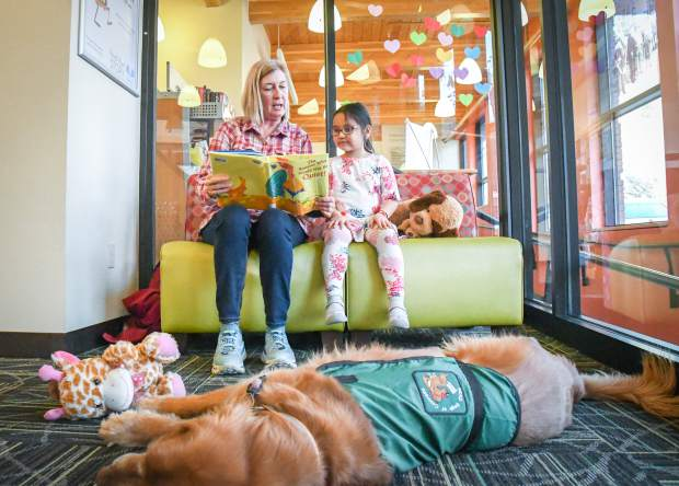 Volunteer Kitty Bearden reads a book to 6-year-old Juliet Magallanes while reading education assistance dog, Bounder, lays back and relaxes during the PAWS to read at the New Castle Branch Library in February.