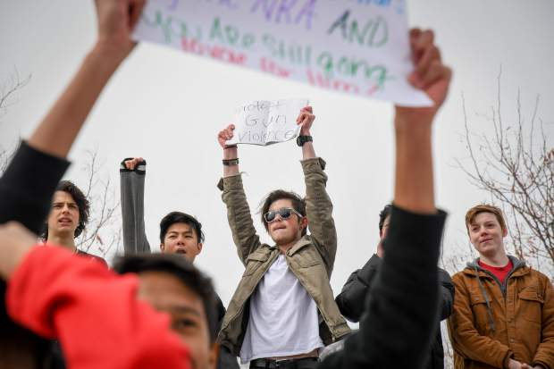 Glenwood Springs High School freshman Johnathon Webster, center, leads his classmates in a chant during the walk out and staged demonstration during their lunch break on a Wednesday in February in support of the Parkland, Florida shooting victims and against the NRA.