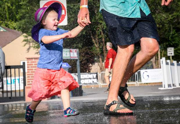 An excited 2-year-old Hazel Grace runs through the water station at the Summer Block Party in downtown Glenwood in August.