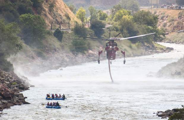 A group of rafters get an unexpected show from a Type I helicopter as it drops into the Colorado River in August after a fire broke out on the hillside near Ami's Acres in West Glenwood.