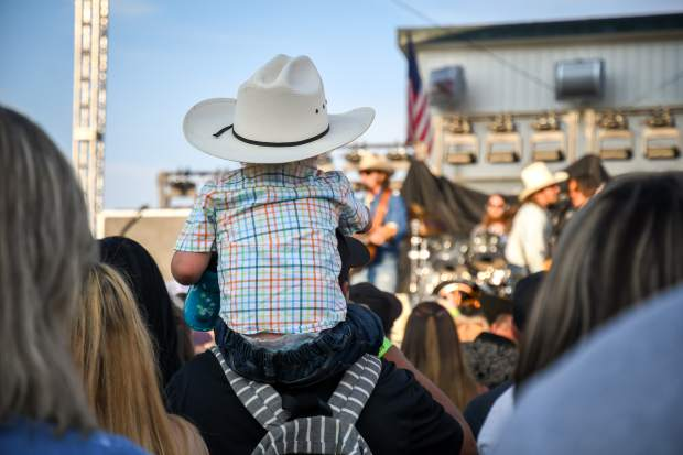 A young cowboy listens to Midland as the band performs during the 2018 Garfield County Fair in August.