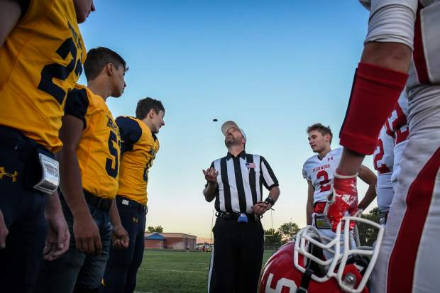 The Glenwood and Rifle captains meet in the middle of the field for the coin toss to start the game in September at Rifle High School.