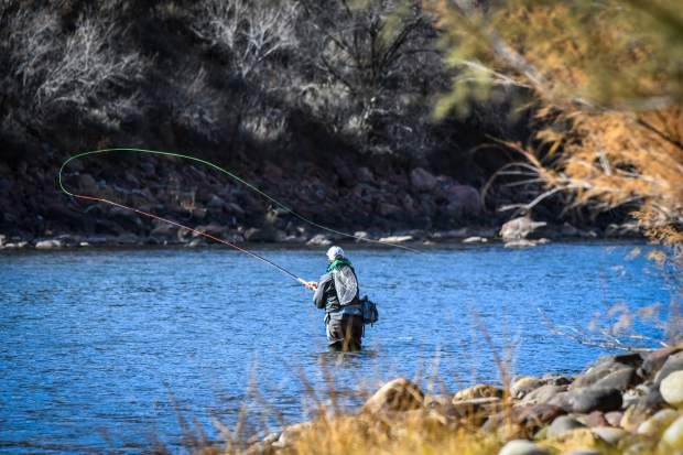 A fly fisherman casts his line in the chilly cold Colorado River in November.