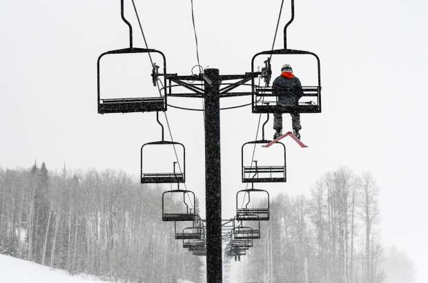 A lone skier heads into the trees on the lift at Sunlight Mountain Resort near Glenwood Springs, Colo on a snowy and cold November morning in November.