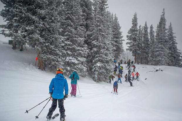 Snowboarders and skiers head toward Highland Bowl right after ski patrol dropped the rope for its opening on opening day at Highlands.