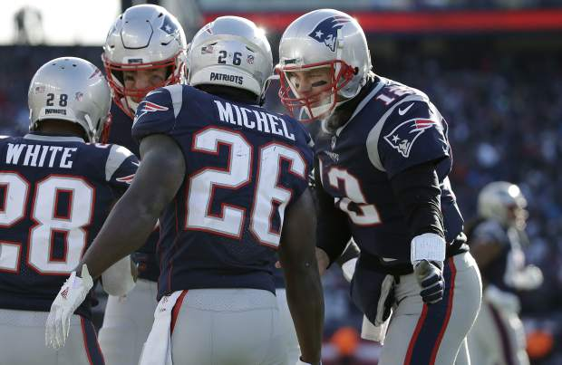 New England Patriots quarterback Tom Brady, right, celebrates a touchdown run by running back Sony Michel (26) during the first half of an NFL divisional playoff football game against the Los Angeles Chargers, Sunday, Jan. 13, 2019, in Foxborough, Mass. (AP Photo/Elise Amendola)