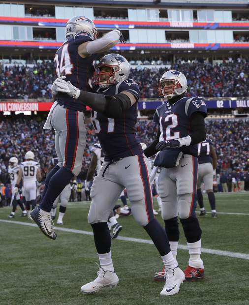 New England Patriots running back Rex Burkhead (34) gets a lift from Rob Gronkowski, center, as Tom Brady (12) joins the celebration after Burkhead's touchdown during the first half of an NFL divisional playoff football game against the Los Angeles Chargers, Sunday, Jan. 13, 2019, in Foxborough, Mass. (AP Photo/Charles Krupa)