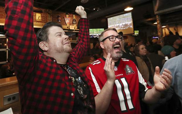 Atlanta Falcons fans Jonathan Springston, left, and Albert Hopkins react as the Los Angeles Rams beat the New Orleans Saints, 26-23, in overtime to win the the NFL football NFC championship game, while watching at Midway Pub in Atlanta on Sunday, Jan. 20, 2019. Falcons fans were dreading their rivals the Saints advancing to the Super Bowl in Atlanta. (Curtis Compton/Atlanta Journal-Constitution via AP)
