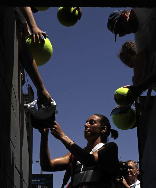 France's Caroline Garcia signs autographs after defeating compatriot Jessika Ponchet during their first round match at the Australian Open tennis championships in Melbourne, Australia, Monday, Jan. 14, 2019. (AP Photo/Kin Cheung)