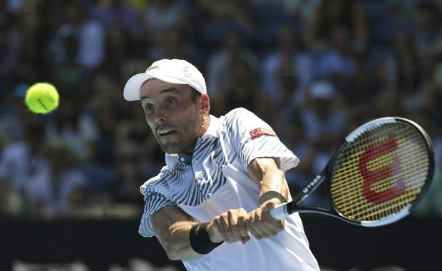 Spain's Roberto Bautista Agut makes a backhand return to Greece's Stefanos Tsitsipas during their quarterfinal match at the Australian Open tennis championships in Melbourne, Australia, Tuesday, Jan. 22, 2019. (AP Photo/Andy Brownbill)