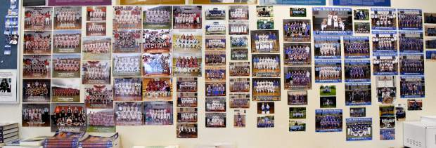 Coach Harvey's wall of team photos dating back to his first year of coaching in 2000.