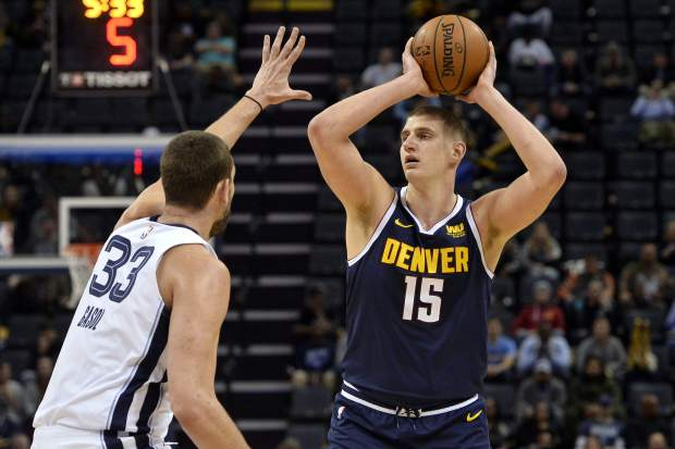 Denver Nuggets center Nikola Jokic (15) handles the ball against Memphis Grizzlies center Marc Gasol (33) in the first half of an NBA basketball game Monday, Jan. 28, 2019, in Memphis, Tenn. (AP Photo/Brandon Dill)