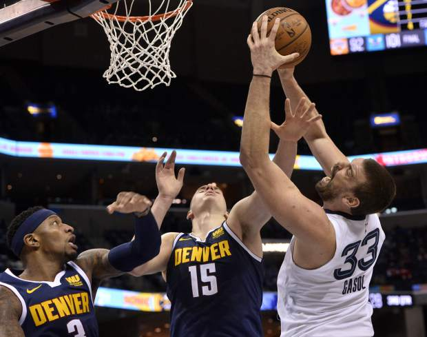 Memphis Grizzlies center Marc Gasol (33) shoots against Denver Nuggets center Nikola Jokic (15) and forward Torrey Craig (3) in the second half of an NBA basketball game Monday, Jan. 28, 2019, in Memphis, Tenn. (AP Photo/Brandon Dill)