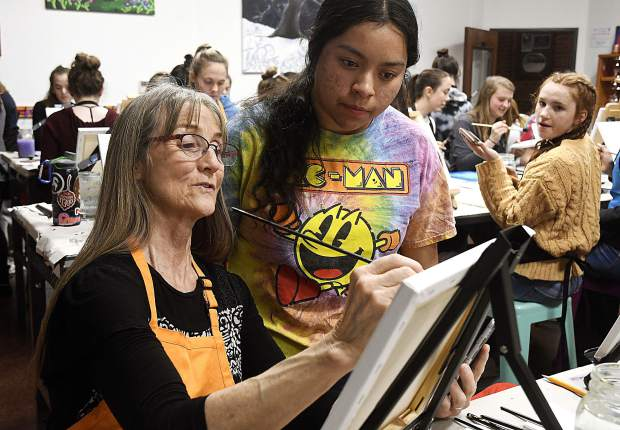 Linda Jabbour helps a player get started as members of the Glenwood Springs High School girls basketball team enjoyed a team bonding paint night last week at Create! Art & Essence art center.