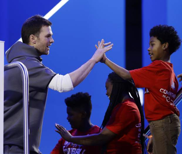 New England Patriots' Tom Brady high fives some kids during Opening Night for the NFL Super Bowl 53 football game Monday, Jan. 28, 2019, in Atlanta. (AP Photo/Matt Rourke)