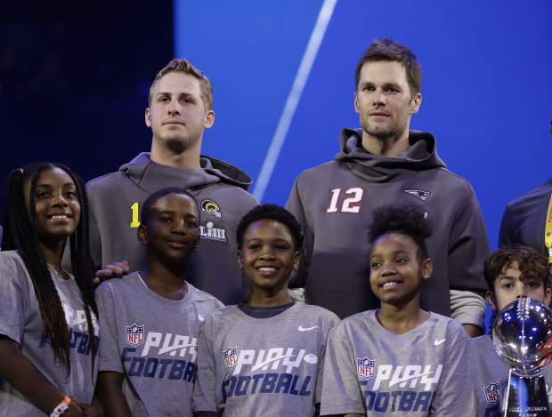 New England Patriots' Tom Brady and Los Angeles Rams' Jared Goff pose for a picture during Opening Night for the NFL Super Bowl 53 football game Monday, Jan. 28, 2019, in Atlanta. (AP Photo/Matt Rourke)
