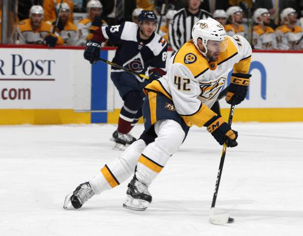Nashville Predators center Colin Blackwell, front, picks up the puck as Colorado Avalanche left wing Matt Nieto pursues in the first period of an NHL hockey game Monday, Jan. 21, 2019, in Denver. (AP Photo/David Zalubowski)