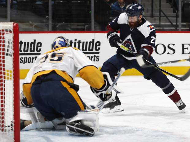 Colorado Avalanche defenseman Ian Cole, right, pursues the puck after a save by Nashville Predators goaltender Pekka Rinne in the first period of an NHL hockey game Monday, Jan. 21, 2019, in Denver. (AP Photo/David Zalubowski)
