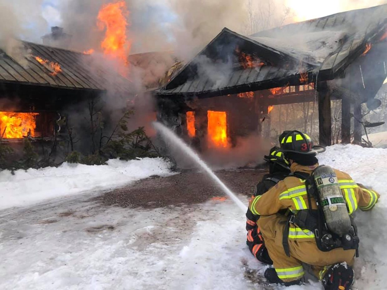 Roaring Fork Fire Rescue firefighters work Tuesday morning to battle a house fire on the east side of Ruedi Reservoir above Basalt.