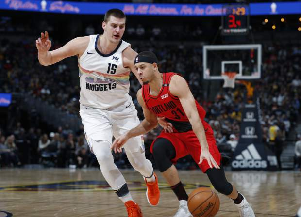 Portland Trail Blazers guard Seth Curry, front, drives to the rim past Denver Nuggets center Nikola Jokic in the second half of an NBA basketball game Sunday, Jan. 13, 2019, in Denver. The Nuggets won 116-113. (AP Photo/David Zalubowski)