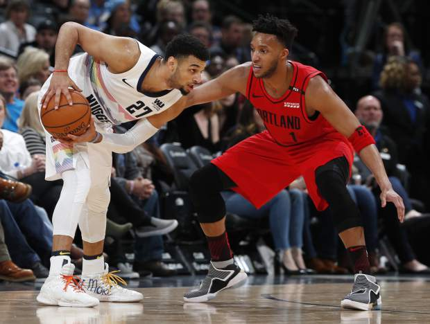 Denver Nuggets guard Jamal Murray, left, looks to pass the ball as Portland Trail Blazers guard Evan Turner defends in the second half of an NBA basketball game Sunday, Jan. 13, 2019, in Denver. The Nuggets won 116-113. (AP Photo/David Zalubowski)