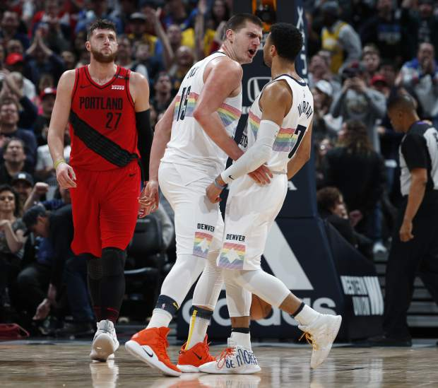 Denver Nuggets center Nikola Jokic, center, celebrates after scoring a basket with guard Jamal Murray, right, as Portland Trail Blazers center Jusuf Nurkic looks on in the second half of an NBA basketball game, Sunday, Jan. 13, 2019, in Denver. The Nuggets won 116-113. (AP Photo/David Zalubowski)