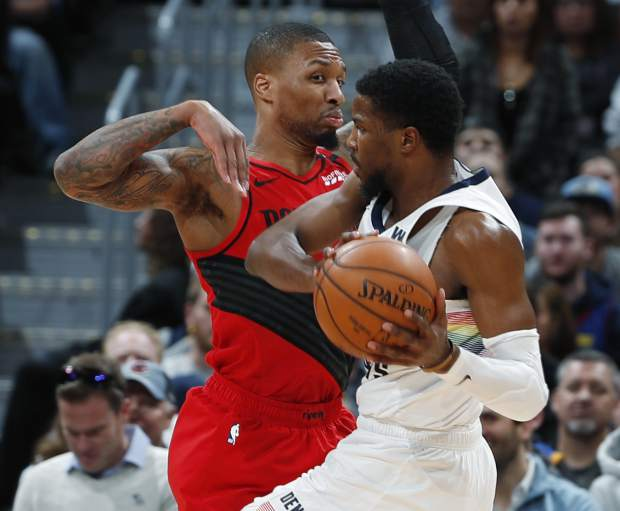 Denver Nuggets guard Malik Beasley, front, drives to the rim as Portland Trail Blazers guard Damian Lillard defends in the second half of an NBA basketball game Sunday, Jan. 13, 2019, in Denver. The Nuggets won 116-113. (AP Photo/David Zalubowski)
