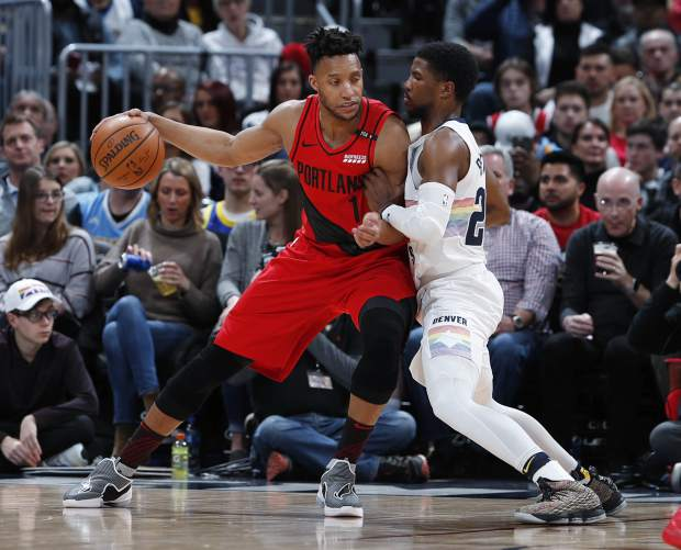 Portland Trail Blazers guard Evan Turner, left, works the ball inside as Denver Nuggets guard Malik Beasley defends in the first half of an NBA basketball game, Sunday, Jan. 13, 2019, in Denver. (AP Photo/David Zalubowski)