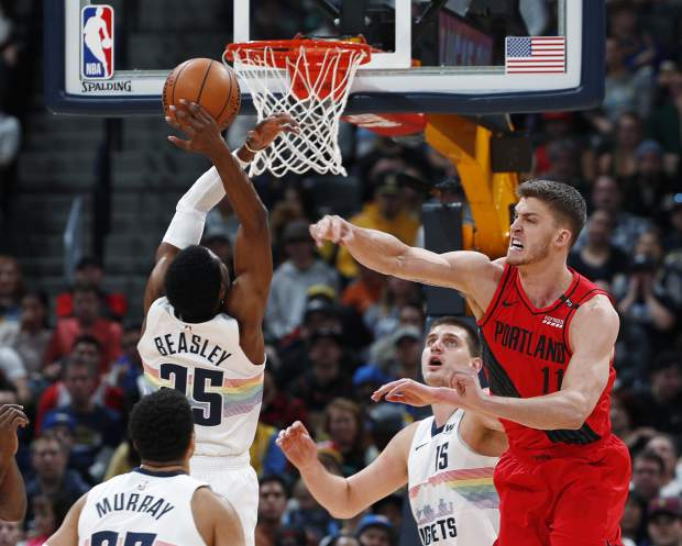 Portland Trail Blazers center Meyers Leonard, right, fights for control of a rebound with Denver Nuggets guard Malik Beasley in the first half of an NBA basketball game, Sunday, Jan. 13, 2019, in Denver. (AP Photo/David Zalubowski)