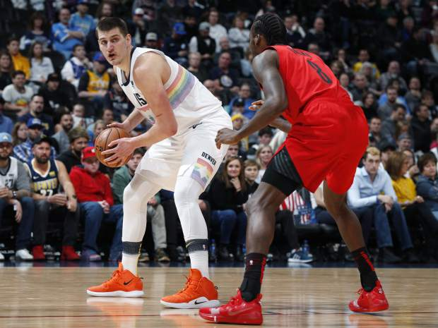 Denver Nuggets center Nikola Jokic, left, looks to pass the ball as Portland Trail Blazers forward Al-Farouq Aminu defends in the first half of an NBA basketball game Sunday, Jan. 13, 2019, in Denver. (AP Photo/David Zalubowski)