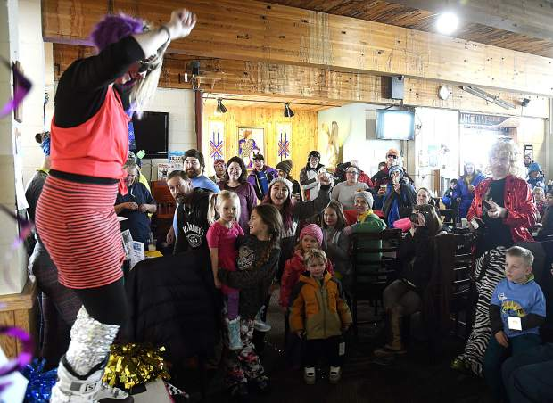 The crowd goes crazy as a contestant shows off her outfit during the '80s costume contest during 34th annual Skier Appreciation Day Friday at Sunlight Mountain Resort.