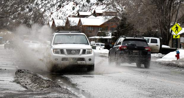 A car hits a large pothole and puddle on South Grand in South Glenwood Springs.