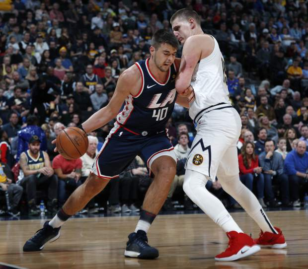 Los Angeles Clippers center Ivica Zubac, left, drives to the rim as Denver Nuggets center Nikola Jokic defends in the first half of an NBA basketball game Sunday, Feb. 24, 2019, in Denver. (AP Photo/David Zalubowski)