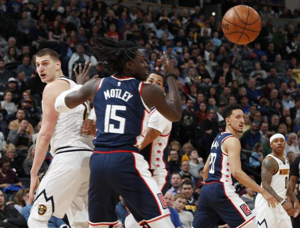 Denver Nuggets center Nikola Jokic, left, throws an over-the-shoulder pass past Los Angeles Clippers forward Johnathan Motley in the second half of an NBA basketball game Sunday, Feb. 24, 2019, in Denver. The Nuggets won 123-96. (AP Photo/David Zalubowski)