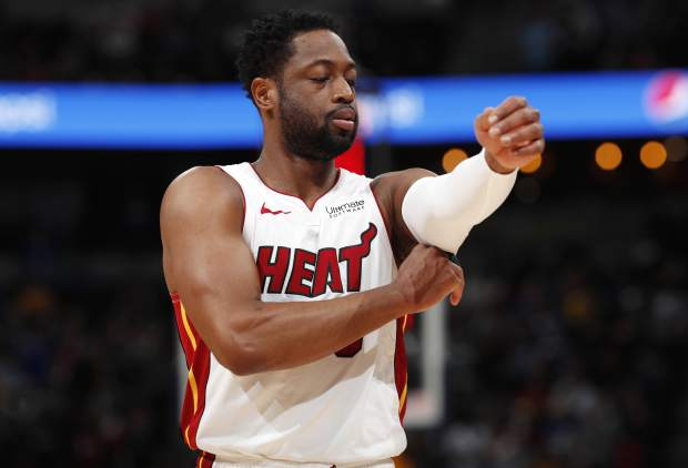 Miami Heat guard Dwyane Wade adjusts his sleeve as he takes the court against the Denver Nuggets in the first half of an NBA basketball game Monday, Feb. 11, 2019, in Denver. (AP Photo/David Zalubowski)