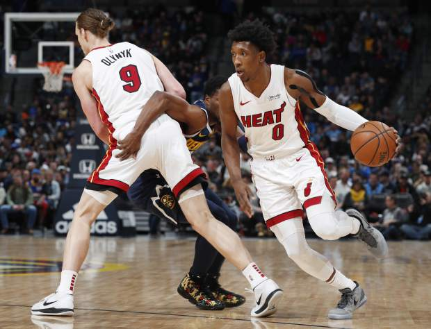 From left, Miami Heat forward Kelly Olynyk sets a pick on Denver Nuggets guard Malik Beasley and allows Miami guard Josh Richardson to drive to the net in the first half of an NBA basketball game Monday, Feb. 11, 2019, in Denver. (AP Photo/David Zalubowski)