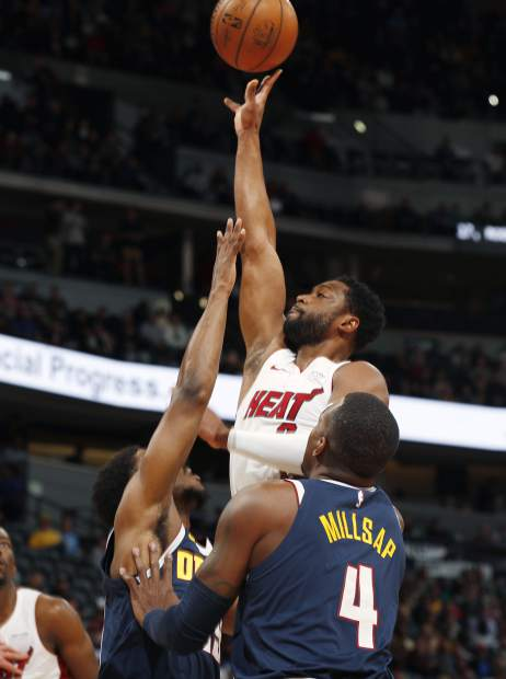 Miami Heat guard Dwyane Wade, center, goes up for a basket between Denver Nuggets guard Malik Beasley, back, and forward Paul Millsap in the first half of an NBA basketball game Monday, Feb. 11, 2019, in Denver. (AP Photo/David Zalubowski)