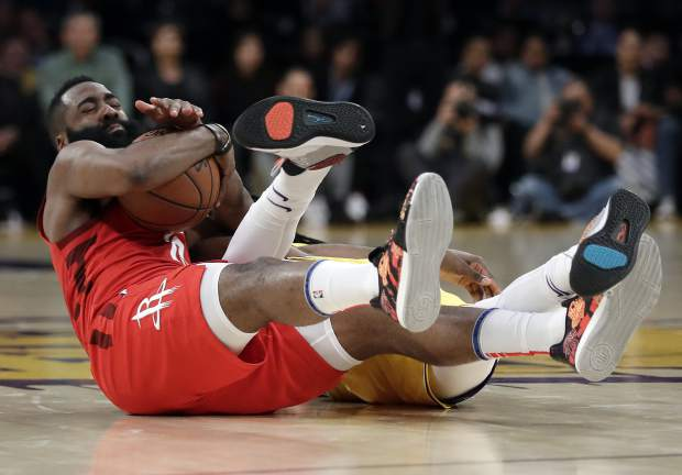 Houston Rockets' James Harden, left, reaches for a loose ball next to Los Angeles Lakers' Reggie Bullock during the second half of an NBA basketball game Thursday, Feb. 21, 2019, in Los Angeles. (AP Photo/Marcio Jose Sanchez)