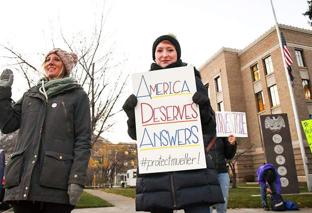Sam Noel holds and sign on the corner of 8th Street and Colorado infront of the Garfield County Courthouse with other protestors during a Pro-Mueller Rally on Thursday eveing.