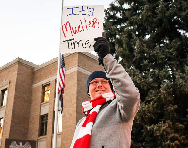 Ryan Folse holds a sign on the corner of Eighth Street and Colorado in front of the Garfield County Courthouse with other protesters during a pro-Mueller rally on Thursday evening.