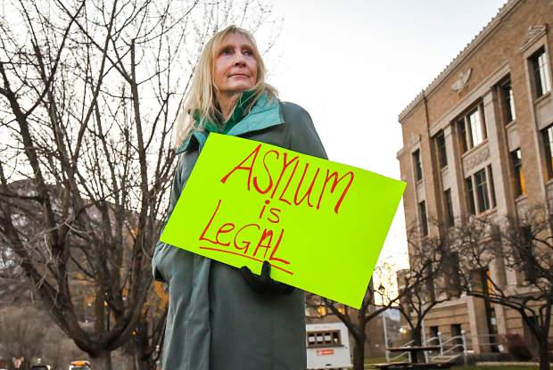 Carolee Murray holds a sign on the corner of Eighth Street and Colorado in front of the Garfield County Courthouse with other protesters during a pro-Mueller rally on Thursday evening.