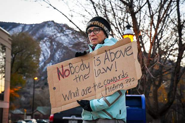 Michele Diamond holds a sign on the corner of 8th Street and Colorado infront of the Garfield County Courthouse with other protestors during a Pro-Mueller Rally on Thursday eveing.
